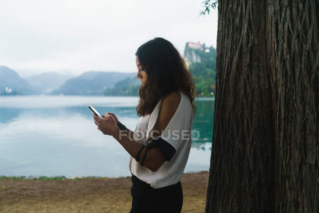 Side view of brunette woman browsing smartphone on lake shore. — Stock Photo