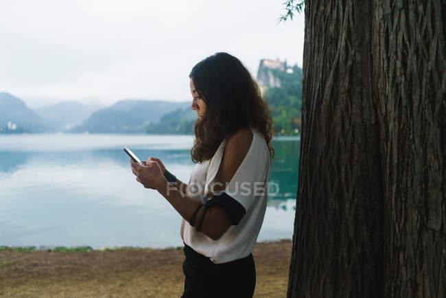 Vista lateral de la mujer morena navegando teléfono inteligente en la orilla del lago . - foto de stock