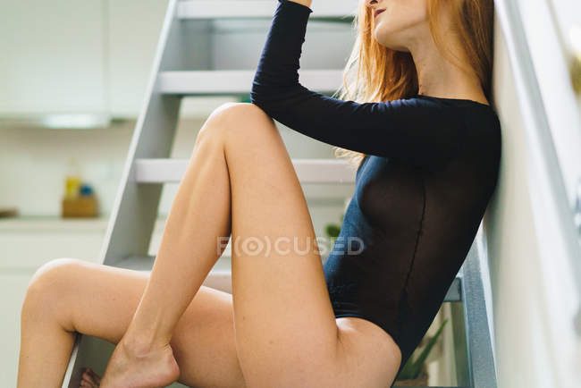 Crop red hair woman posing on stairs woman sitting on stairs — Stock Photo