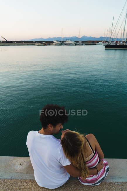 Vue arrière du couple heureux assis sur la jetée et s'amusant — Photo de stock