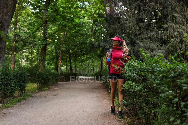 Sportswoman walking with bottle of water after workout in park — Stock Photo