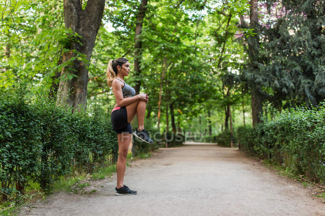Side view of athletic girl warming up leg before jogging on park alley — Stock Photo