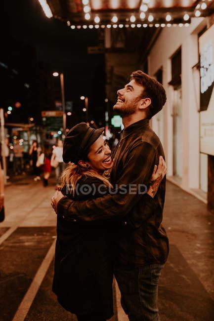 Coppia che abbraccia e ride sulla strada serale — Foto stock