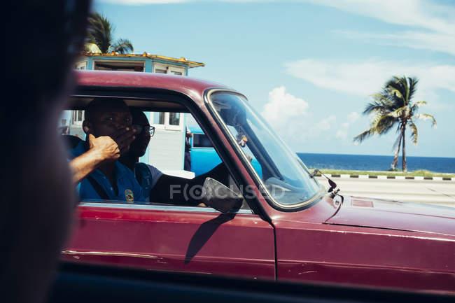 CUBA - 27 DE AGOSTO DE 2016: Gente haciendo gestos en coche pasando por la cámara en la carretera - foto de stock