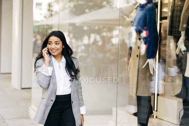 Портрет предприниматель пешком вдоль витрин и говоря телефон — стоковое фото