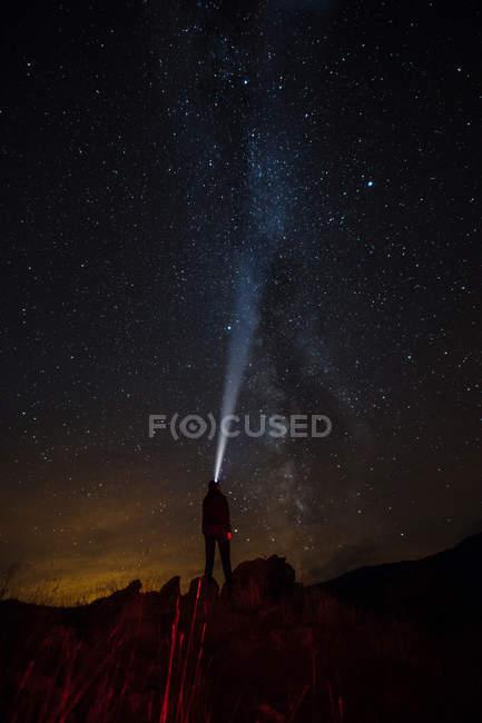 Задній вид на людину, стоячи на скелі і освітлення з ліхтарик, щоб Чумацького шляху — стокове фото