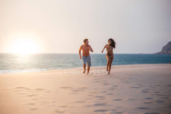 Coppie multiracial felici che funzionano sulla spiaggia tropicale romantica — Foto stock