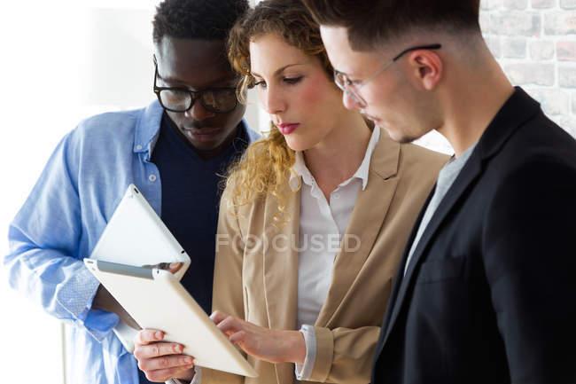 Portrait de groupe de gens d'affaires regardant tablette dans les mains d'un collègue au bureau . — Photo de stock