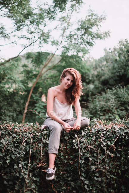 Portrait young woman sitting on garden fence and looking at camera — Stock Photo
