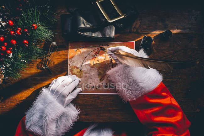 Урожай Санта Клаус руки рисунок с перо подарок доставки маршруты на карте мира — стоковое фото
