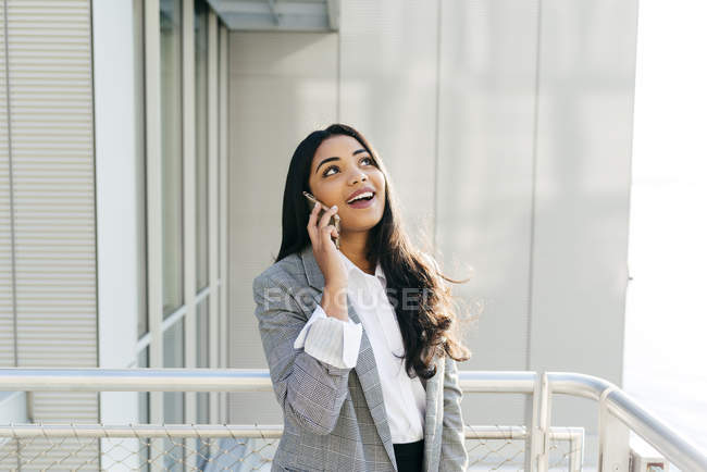 Cheerful businesswoman in jacket talking on phone at balcony — Stock Photo