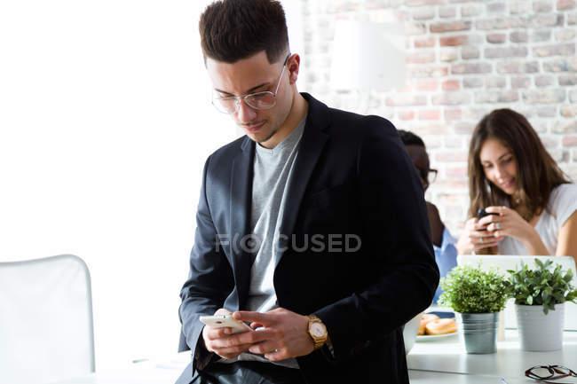 Portrait of businessman using smartphone in loft office. — Stock Photo