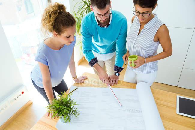 Grupo de gente de negocios mirando hojas de papel en la mesa en la oficina moderna . - foto de stock