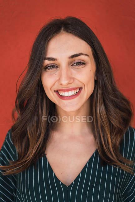 Портрет улыбающейся брюнетки в полосатом платье на красном фоне — стоковое фото
