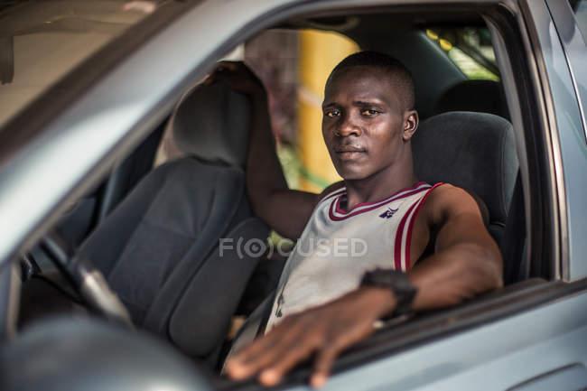 BENIN, ÁFRICA - AGOSTO 31, 2017: Retrato de um homem sentado no carro em casa do motorista e olhando para a câmera . — Fotografia de Stock