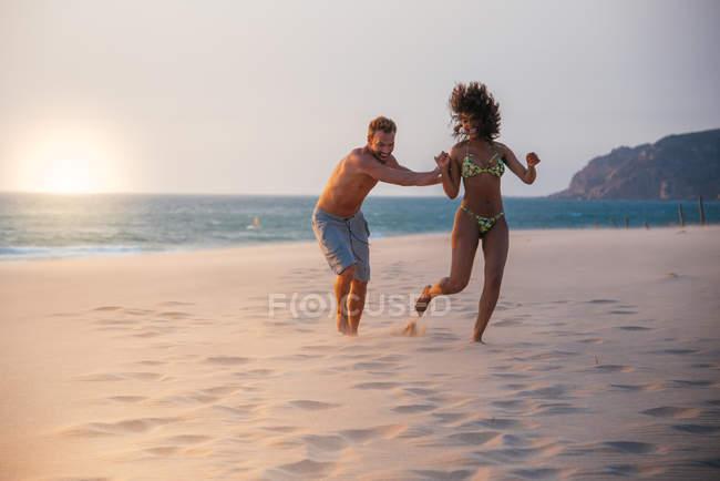 Coppie felici divertendosi sulla spiaggia tropicale romantica — Foto stock