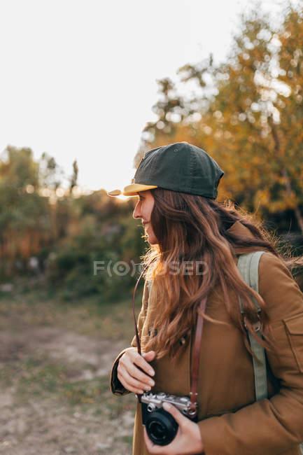 Ritratto di donna bruna che indossa berretto e cappotto che tiene la fotocamera e guarda da parte la campagna — Foto stock