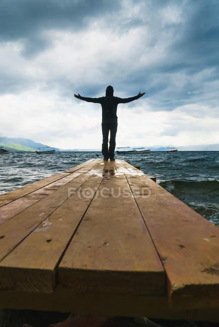 Vue arrière de la silhouette masculine bénéficiant d'une vue sur la tempête dans la mer et les nuages dans le ciel . — Photo de stock