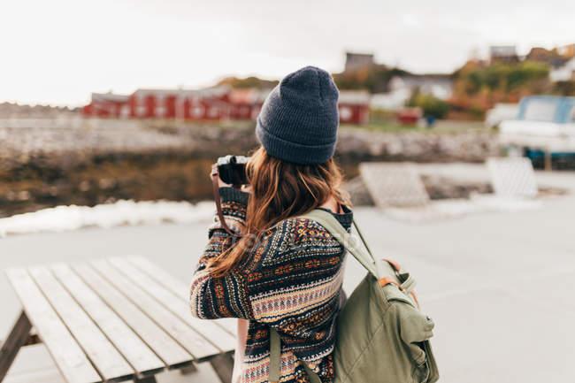 Vue arrière de la femme avec sac à dos, prendre des photos sur l'appareil photo en mains — Photo de stock
