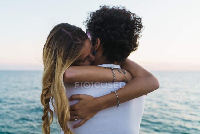 Joven pareja feliz abrazando en el muelle sobre el mar de telón de fondo - foto de stock