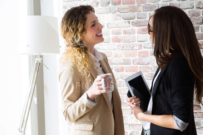 Вид сбоку двух бизнесвумен, весело говорить в офисе — стоковое фото
