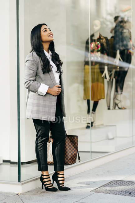 Portrait of businesswoman wearing jacket posing near shop window — Stock Photo