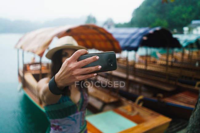 Портрет, жінки, беручи selfie поблизу човнах на озері — стокове фото