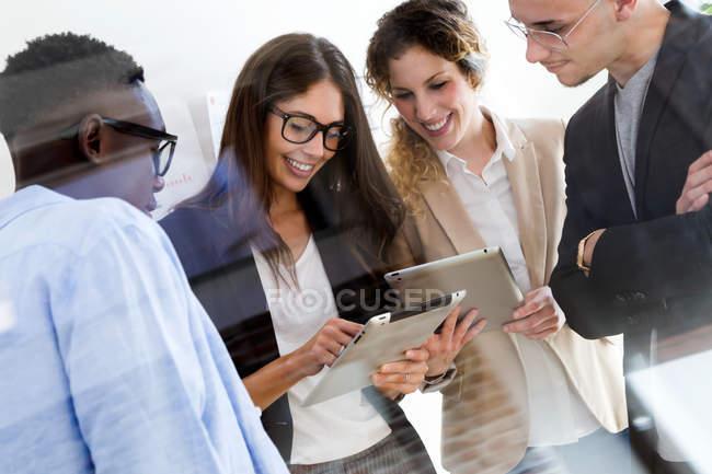 Vue à travers le verre du groupe de gens d'affaires utilisant des tablettes dans le bureau moderne — Photo de stock