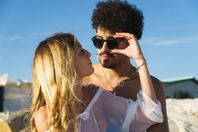 Young girl over shoulder adjusting sunglasses on stylish boyfriend — Stock Photo