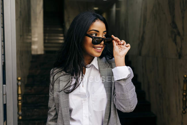Stylish woman wearing jacket putting on sunglasses — Stock Photo
