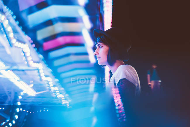 Side view woman posing in illuminated night park — Stock Photo