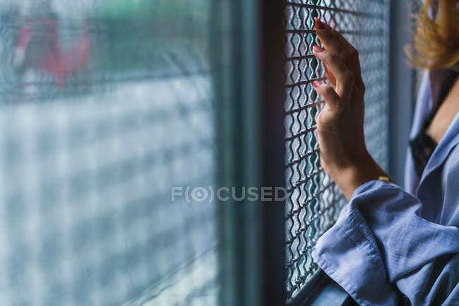 Crop female hand on window grid — Stock Photo