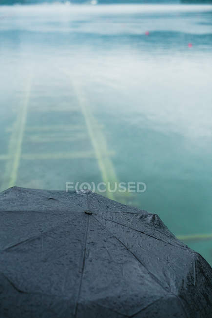 High angle crop of umbrella over lake with railways under turquoise water — Stock Photo