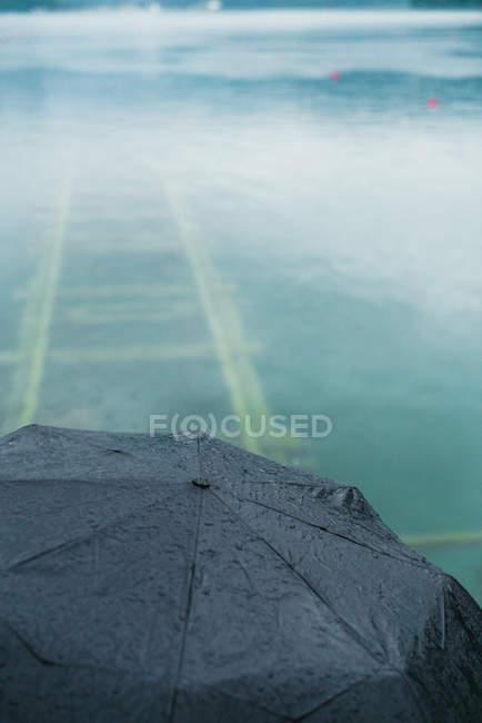 Cultivo de alto ángulo de paraguas sobre el lago con vías férreas bajo agua turquesa - foto de stock