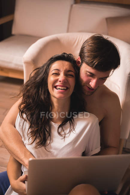 Cheerful people sitting in armchair and browsing laptop. — Stock Photo