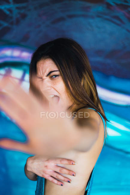 Side view of young brunette woman covering breasts and hiding from camera. — Stock Photo