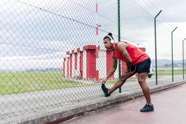 Esportista ouvir música e alongamento perna antes do treino — Fotografia de Stock