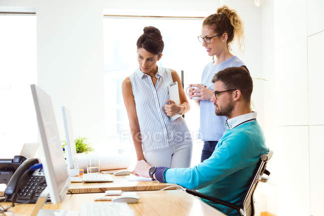 Group of business people looking in monitor in modern office. — Stock Photo