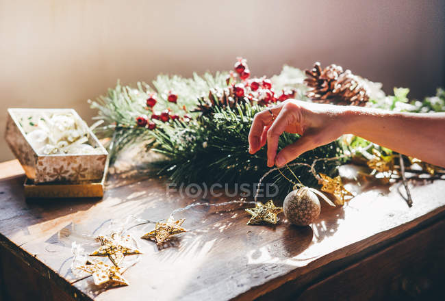Crop Of Female Hands Crafting Christmas Decorations On Table Red