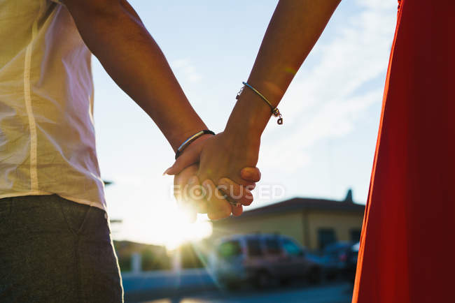 Crop hands of couple posing in bright sunlight at street scene — Stock Photo