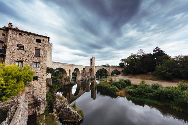 Paisaje nuboso dramático bajo el puente medieval del castillo medieval - foto de stock