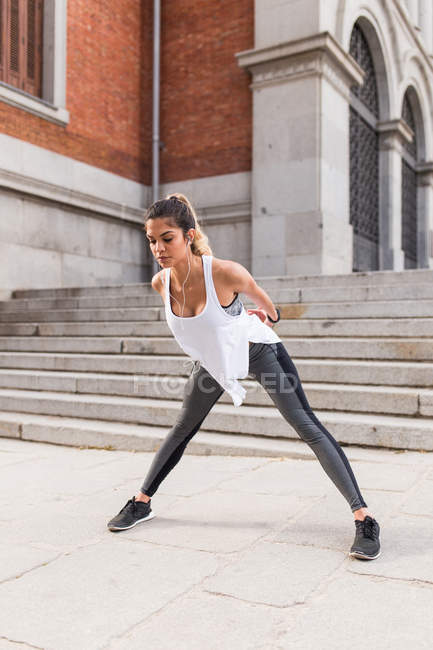 Sportive girl stretching and warming up before jogging at street scene — Stock Photo