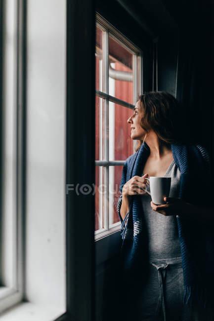Femme avec tasse regardant dans la fenêtre — Photo de stock