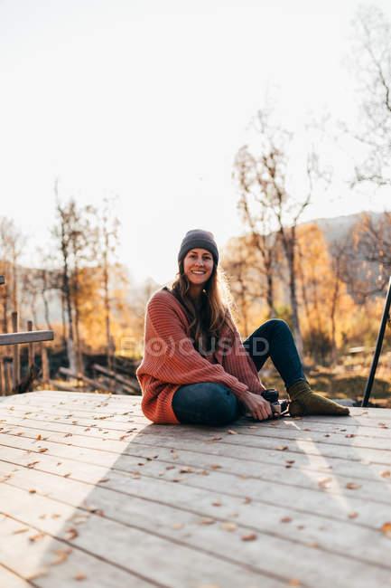 Mulher morena de chapéu sentado no terraço no campo de outono — Fotografia de Stock