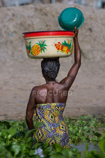 BENIN, AFRICA - AUGUST 30, 2017: Back view of African woman in pond holding big bowl on head. — Stock Photo