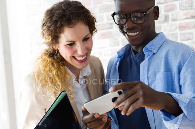 Портрет весела людина, показ екрану смартфона колега в офісі — стокове фото