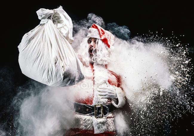 Gritando Santa Claus sosteniendo saco sobre explosiones de nieve - foto de stock