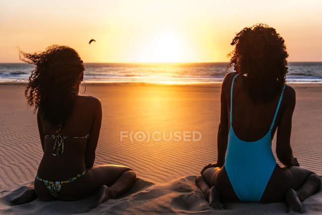 Vista posteriore della donna che si siede sulla spiaggia tropicale e ammirando il volo degli uccelli sul tramonto marino — Foto stock