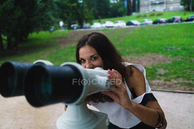 Fröhliche brünette Frau mit Fernglas und Blick in die Kamera — Stockfoto