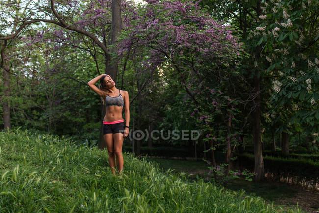 Sporty girl posing on lawn beside purple blooming tree — Stock Photo